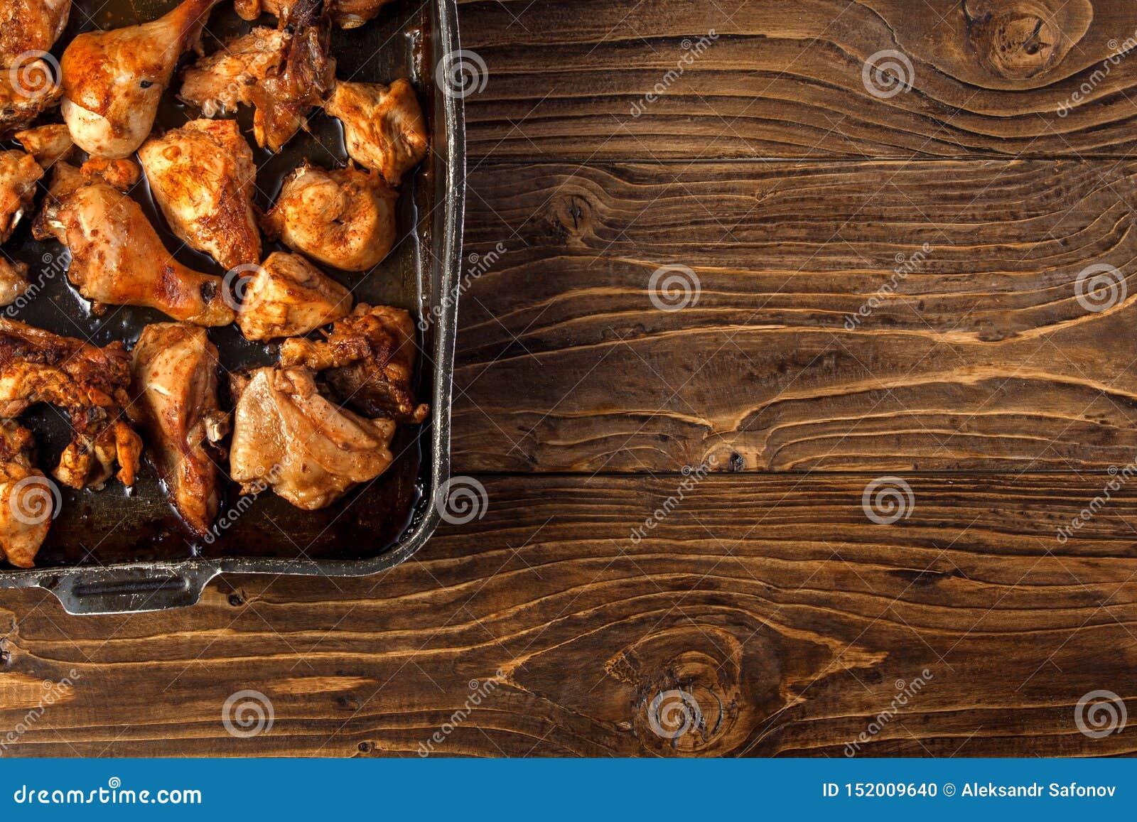 Pezzi al forno del pollo sullo strato di cottura