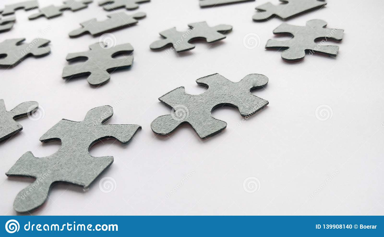 Pezzi grigi astratti del puzzle su fondo bianco
