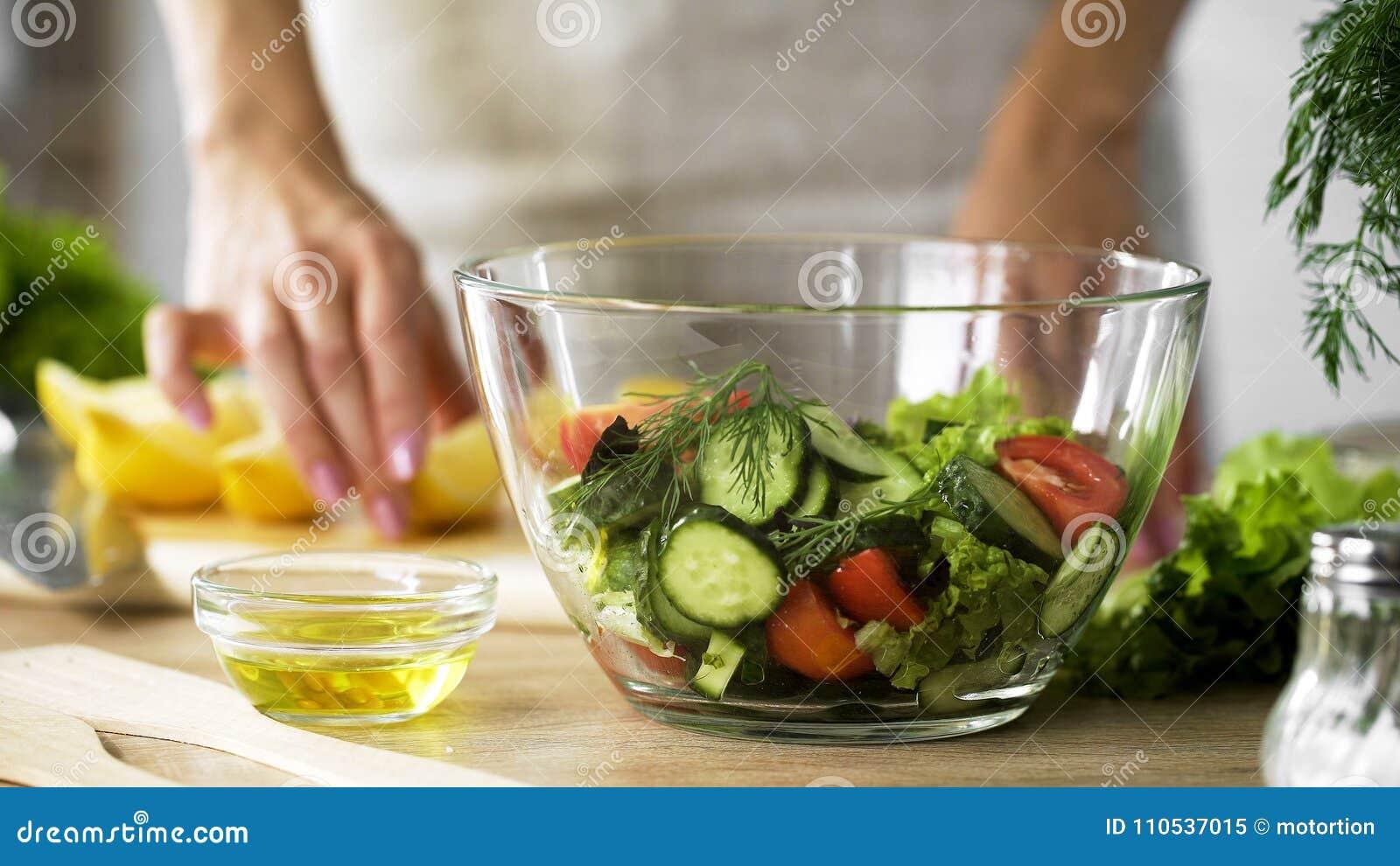 Pezzo del limone della tenuta di signora e olio d oliva per vestirsi, insalatiera organica sulla tavola