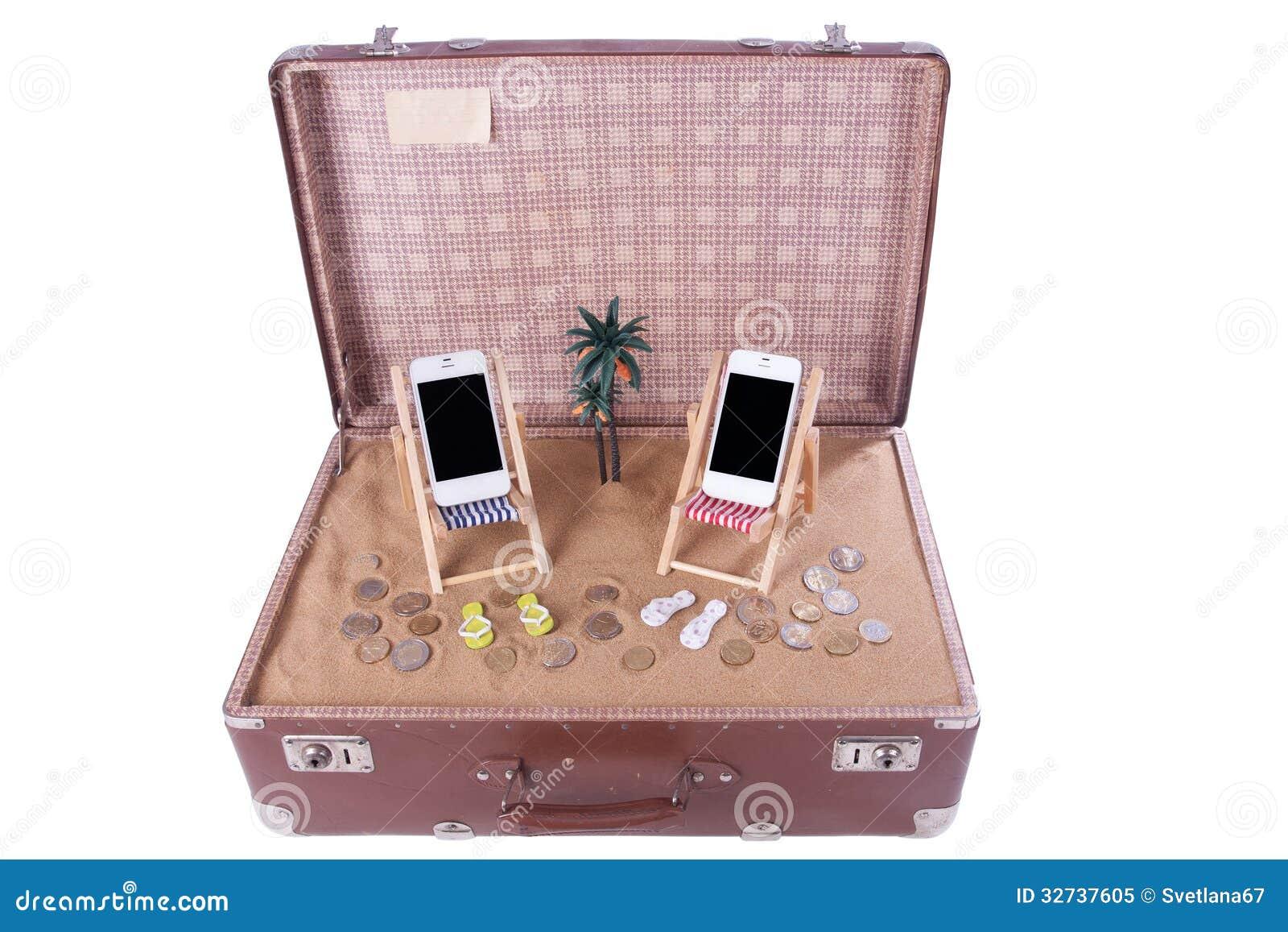 Valigia di cuoio d'annata con due sedie di spiaggia del giocattolo ...