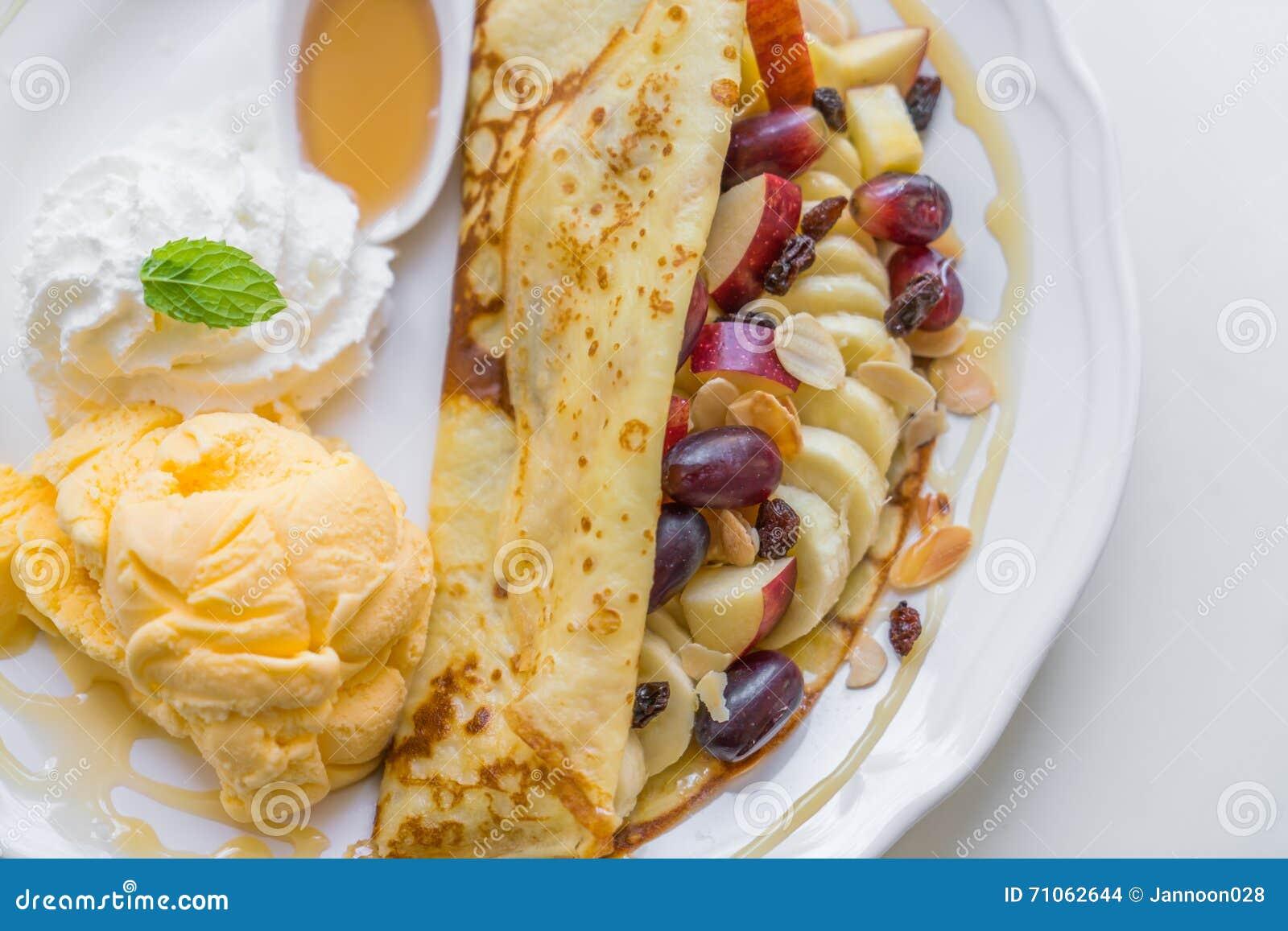 Pfannkuchen und Frucht mit Eiscreme auf Tabelle