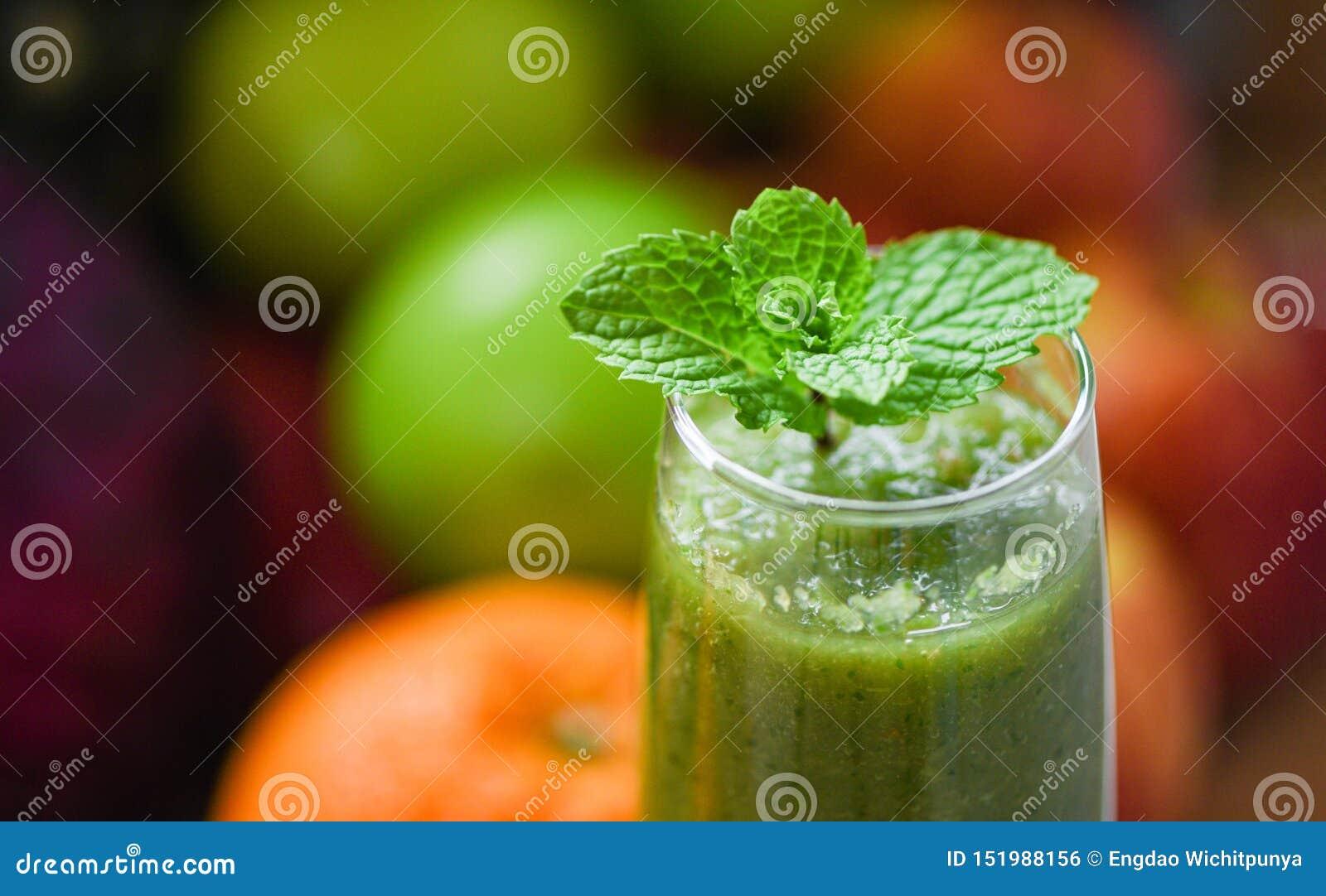 Pfefferminztee - grünes tadelloses Blatt auf Frischgemüsesaft Smoothie- und Sommerfruchthintergrund