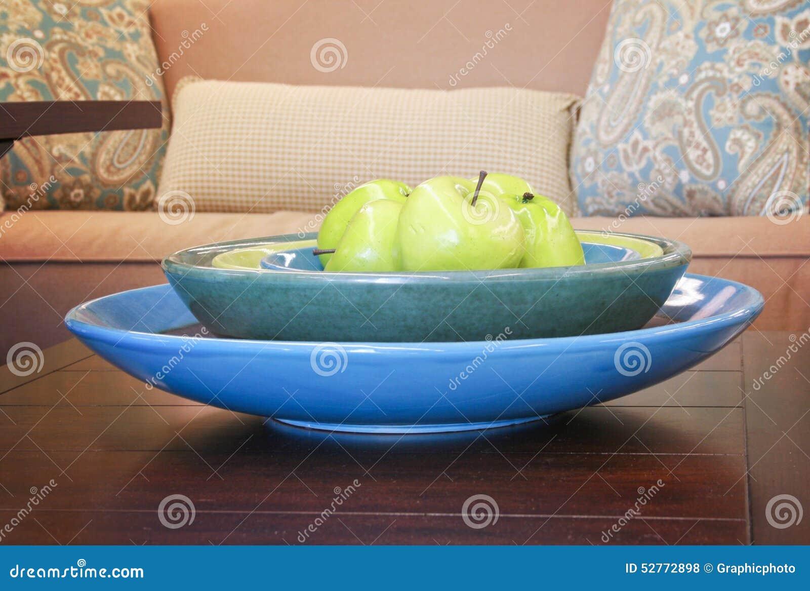 Äpfel in einer schüssel auf einem holztisch in einem wohnzimmer ...
