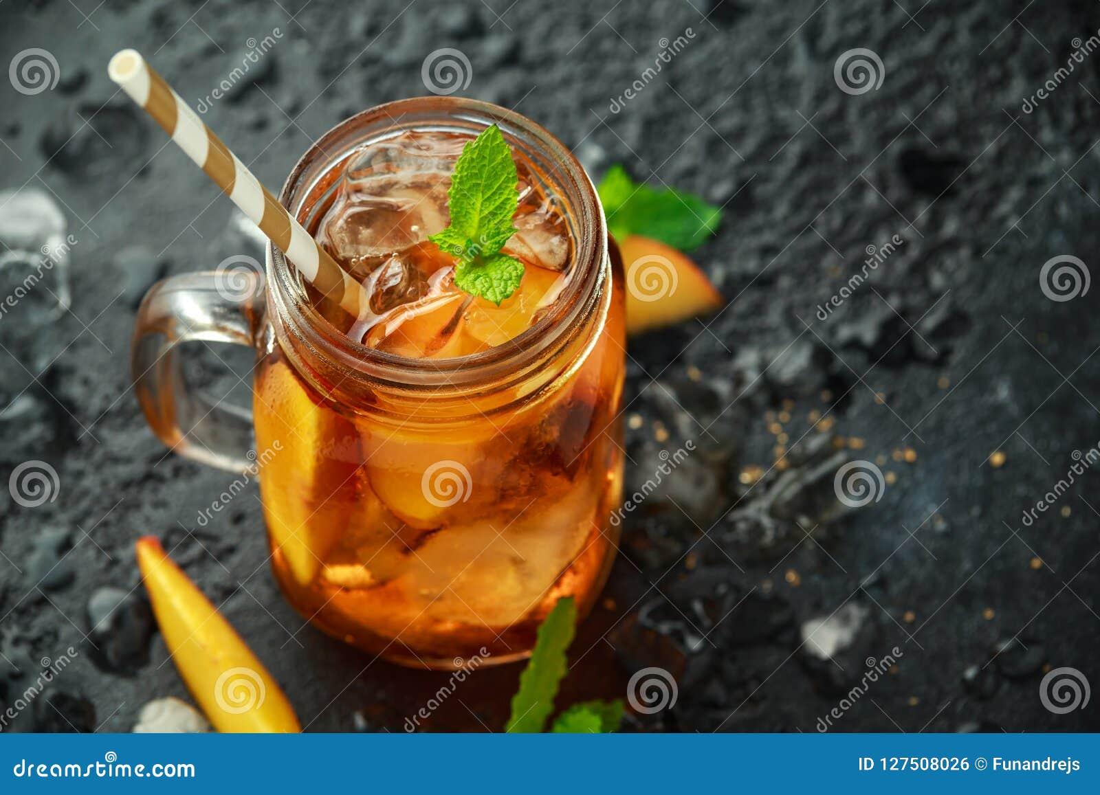Pfirsich-Eistee mit Minze im Glasgefäß, auf rustikalem schwarzem Hintergrund Sommerfrucht-Kältegetränke
