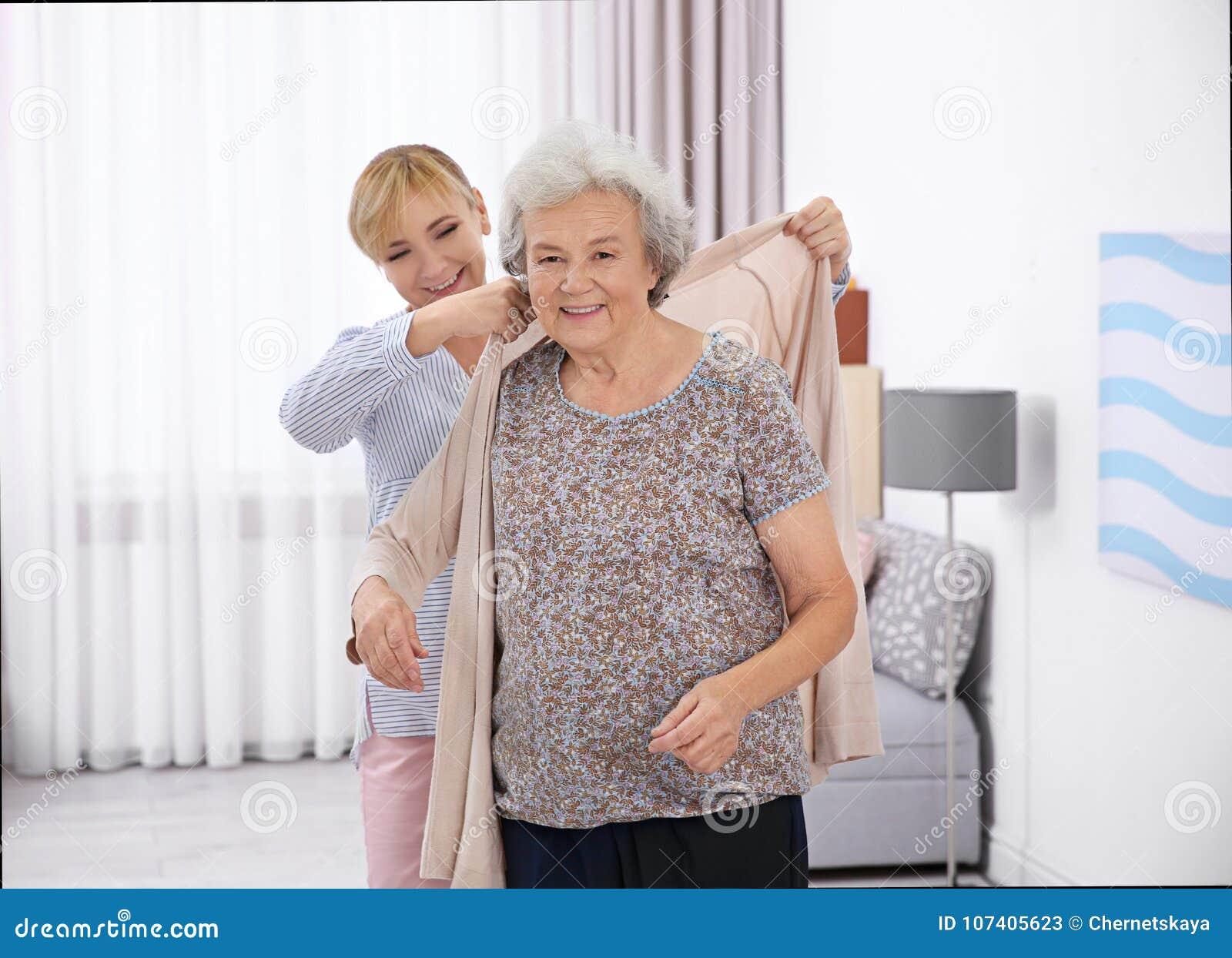 Pflegekraft, die älterer Frau hilft, Wolljacke an zu setzen