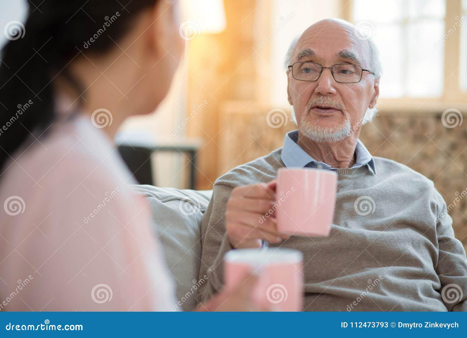 Pflegekraft und reizend älterer Mann, die Erfahrung austauschen
