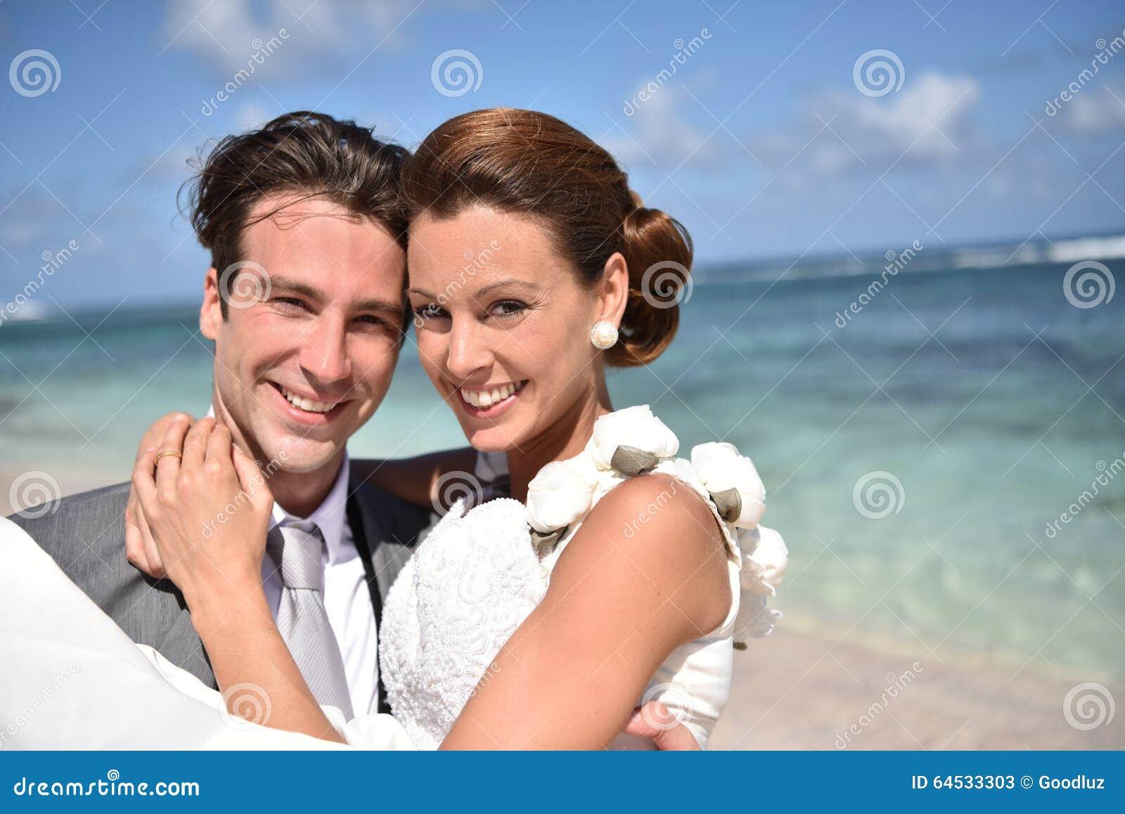 Pflegen Sie das Halten der Braut in seinen Armen auf dem Strand