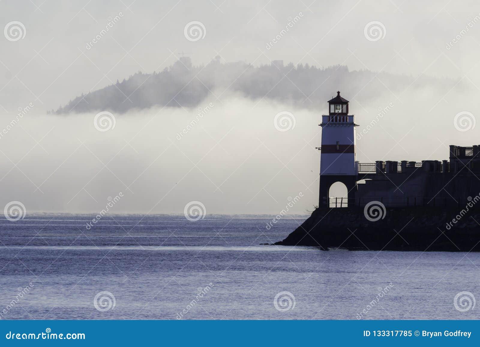 Phare entouré par le brouillard avec la colline à l arrière-plan