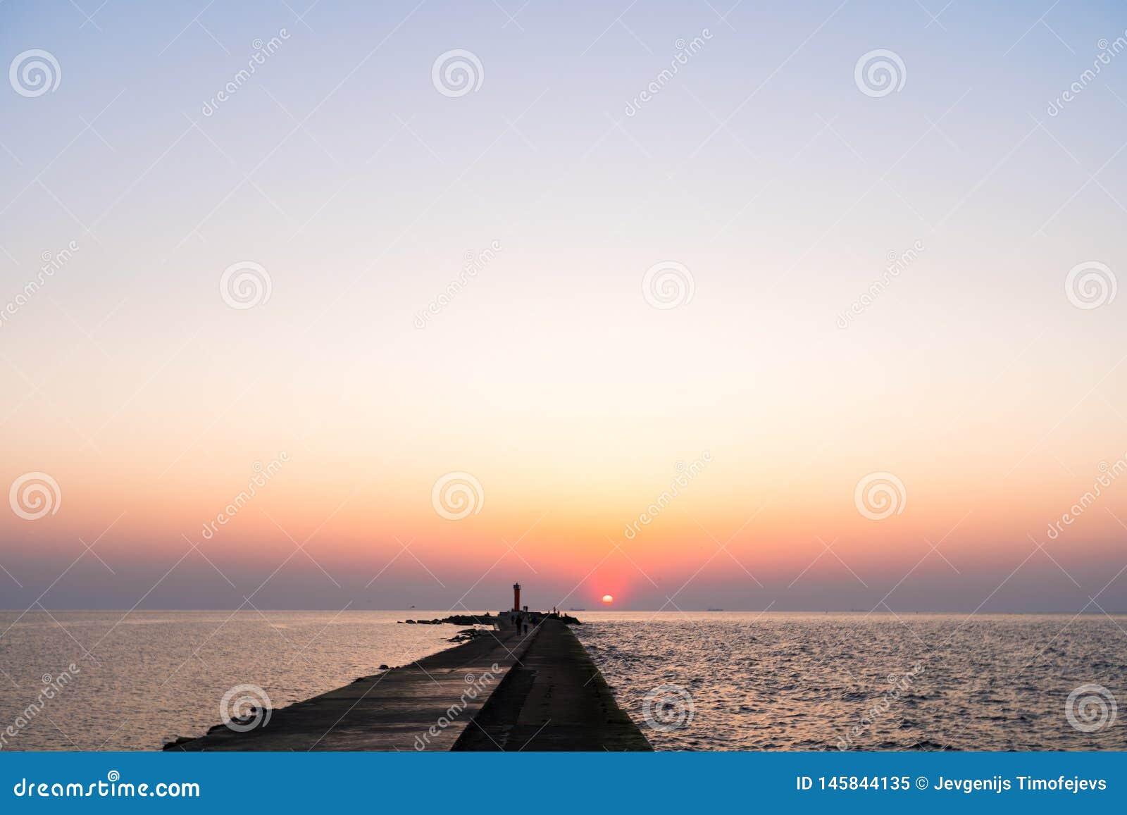 Phare pendant un de derni?re minute du coucher du soleil avec un grand soleil pr?s de l horizon et du ciel clair