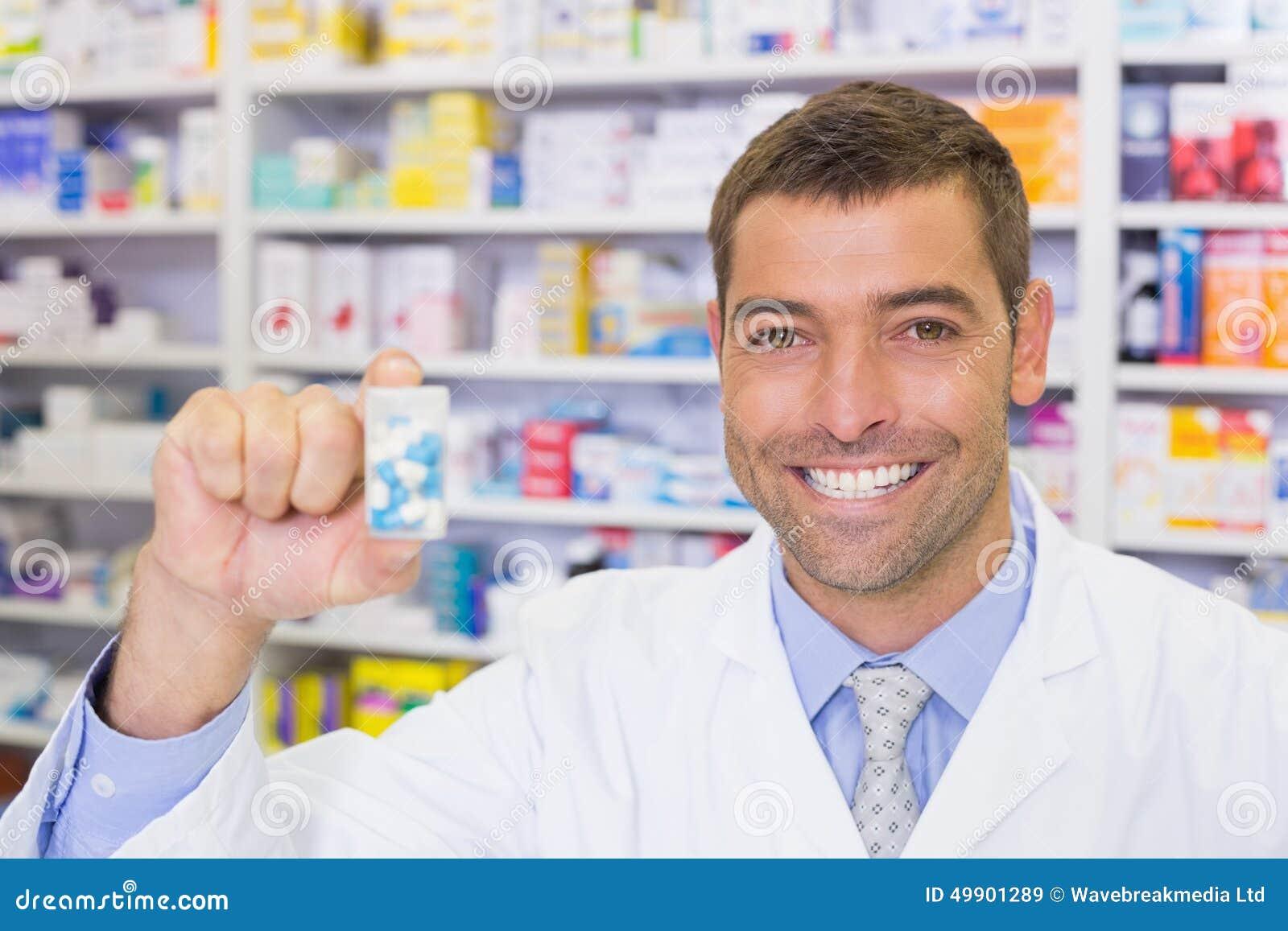 Pharmacien beau montrant le pot de médecine