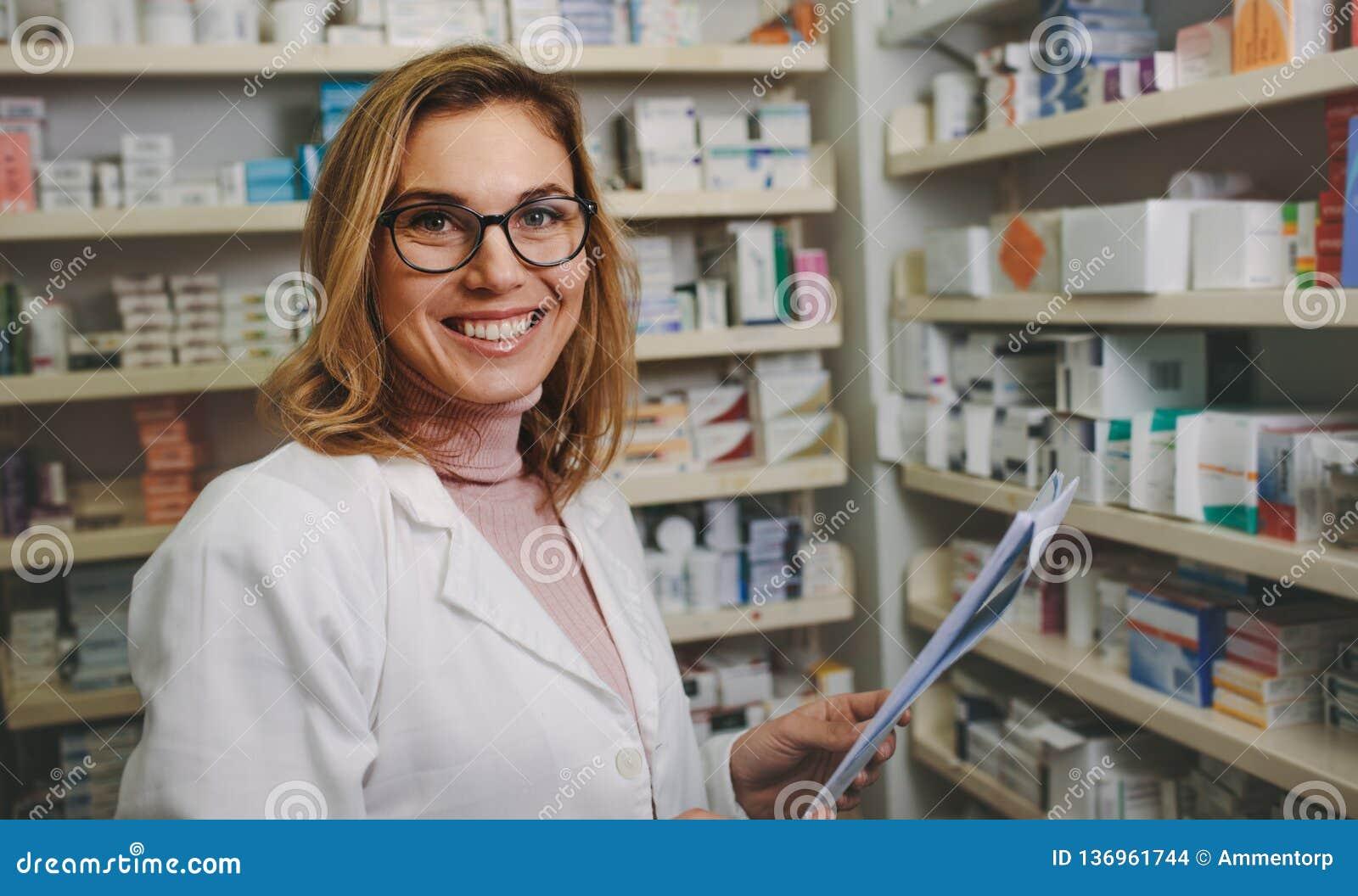 Pharmacien féminin positif travaillant dans la pharmacie