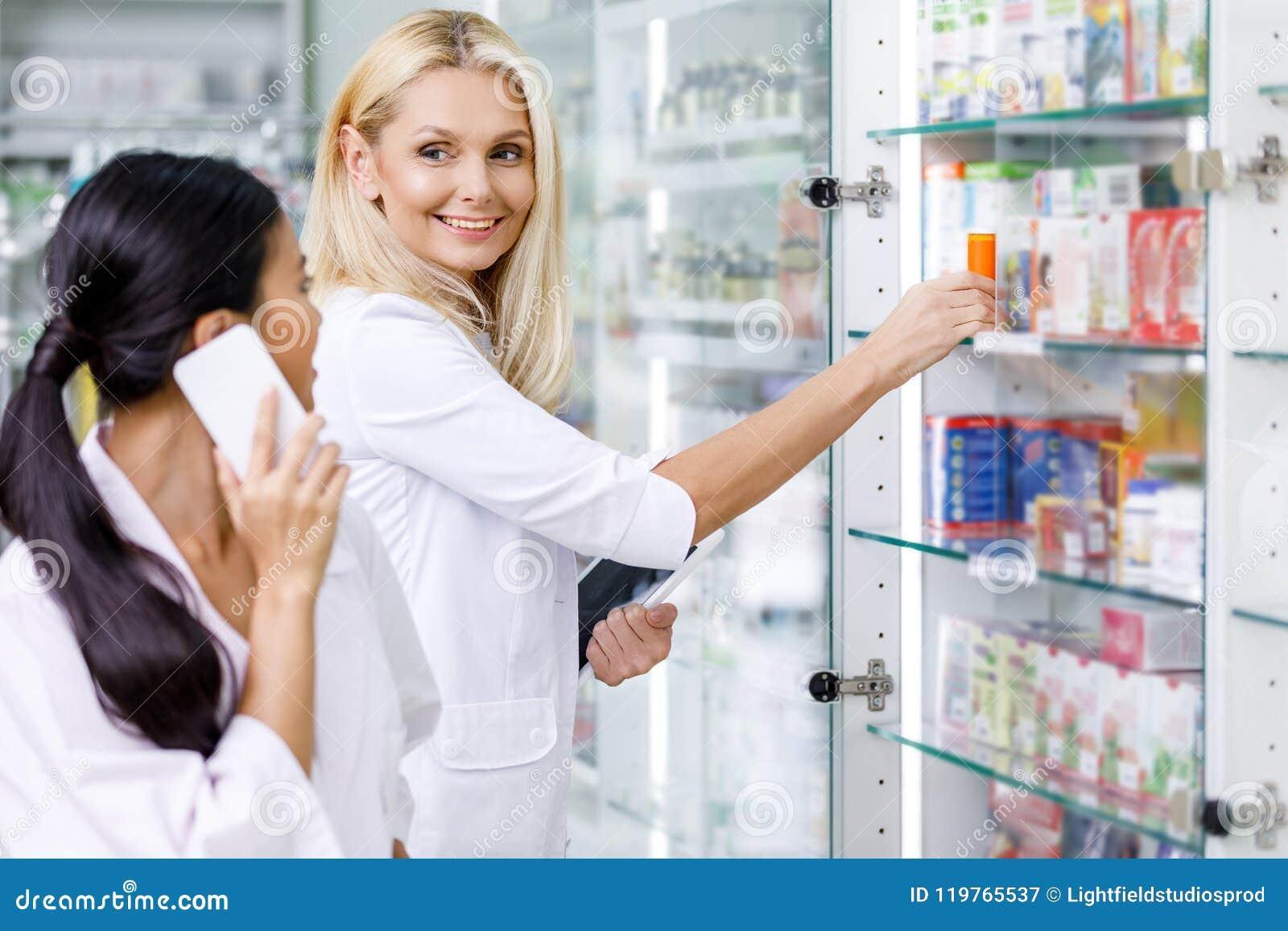 Pharmaciens à l aide des dispositifs numériques et se souriant