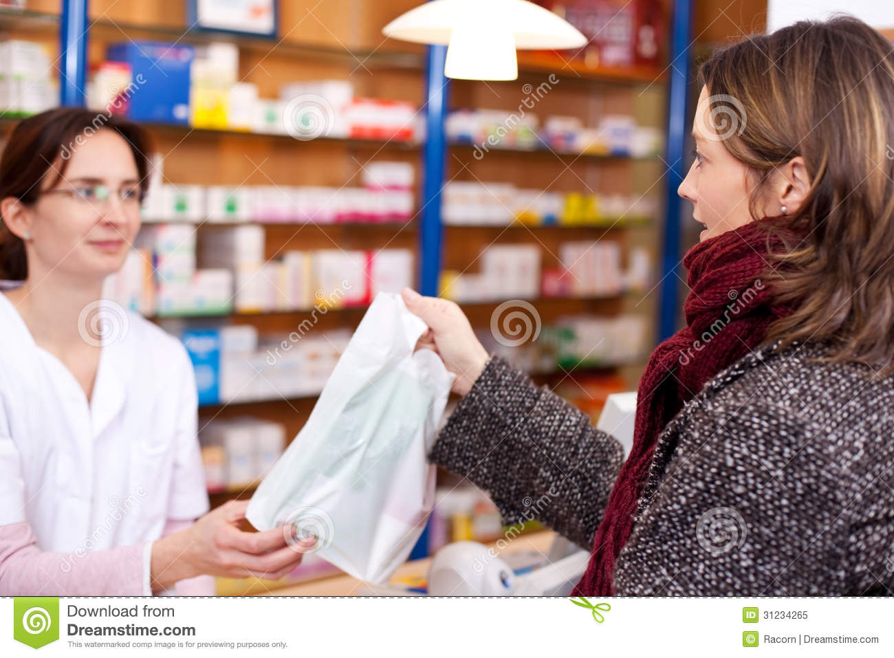w in pharmacy being counseled by s lady stock photo pharmacist passing bag of medicine bag to female customer royalty stock photo