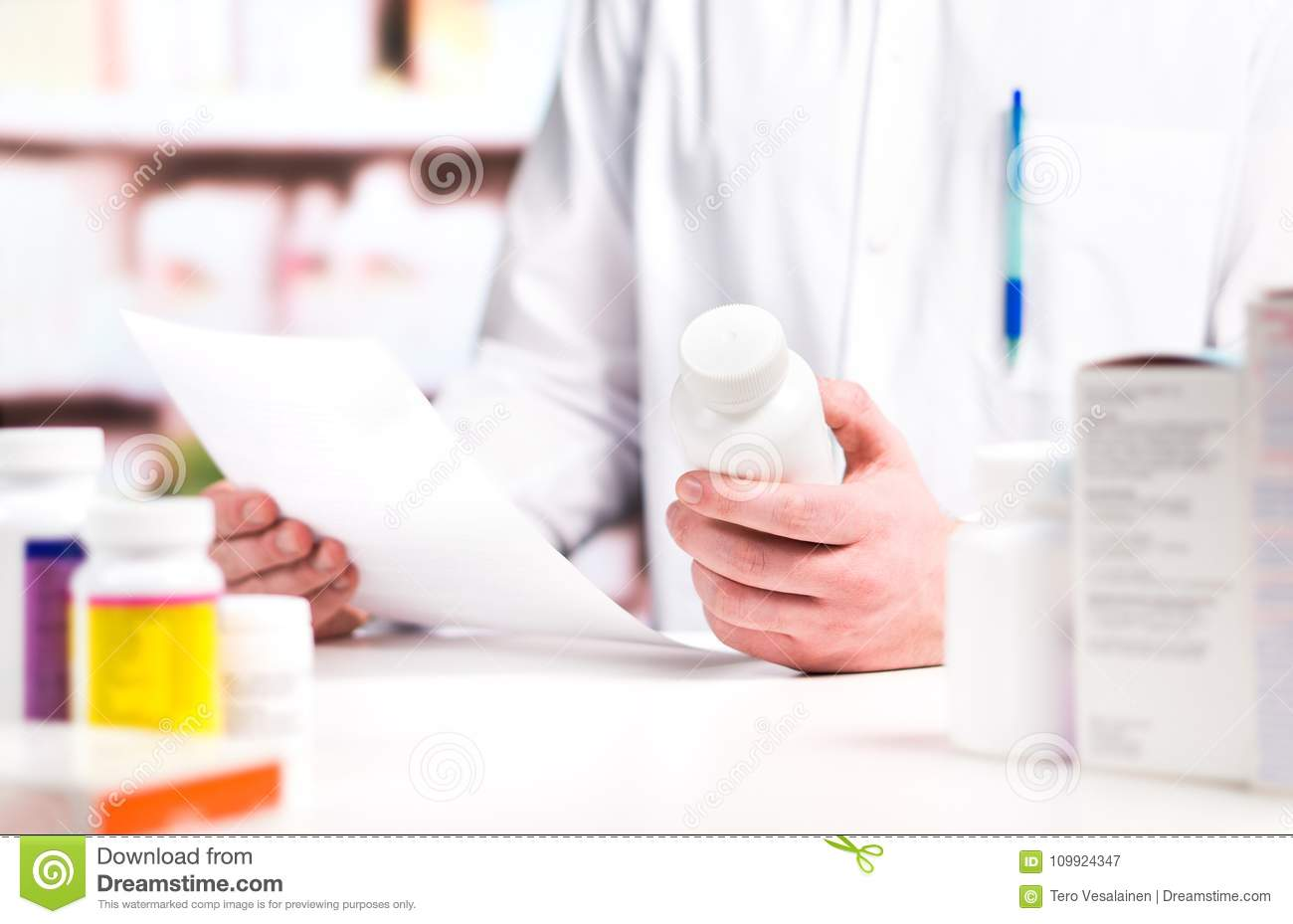 Pharmacist reading prescription with medicine and pill bottle