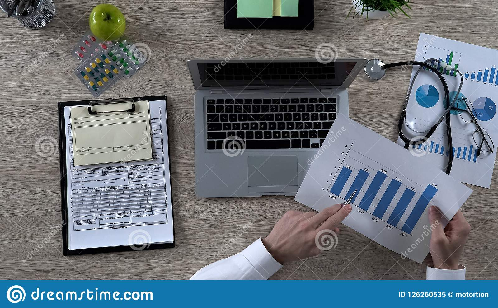 Pharmacist studying statistics of medicine sales, pharmaceutical market research