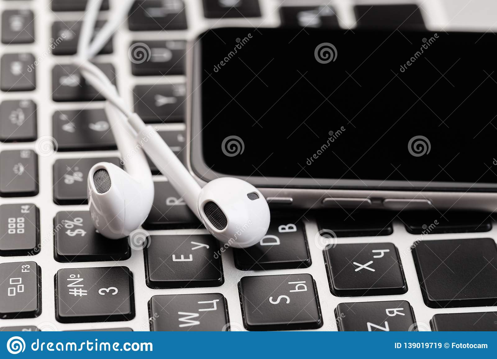Phone with white headphones on laptop keyboard
