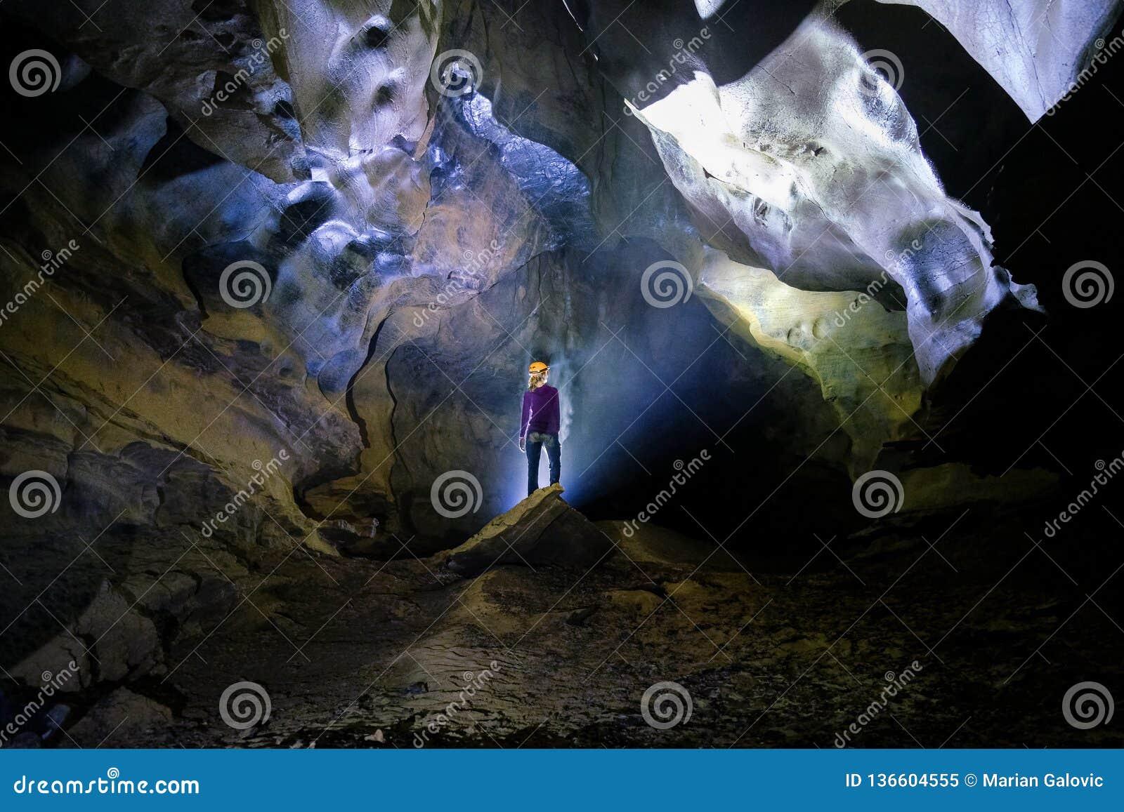 Phong Nha Ke国立公园/越南,15/11/2017:在一个岩石的由后面照的妇女身分在Phong Nha Ke的吊连队洞里面