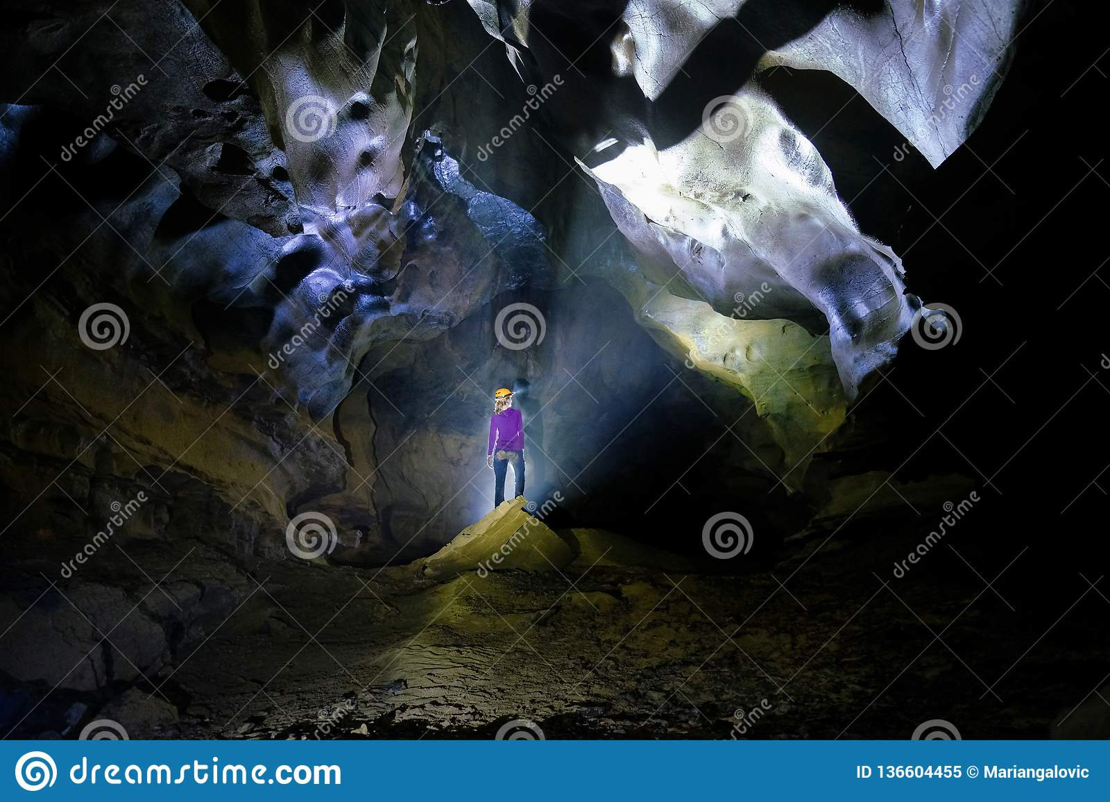 Phong Nha Ke national park / Vietnam, 15/11/2017: Backlit woman standing on a rock inside the Hang Tien cave in the Phong Nha Ke