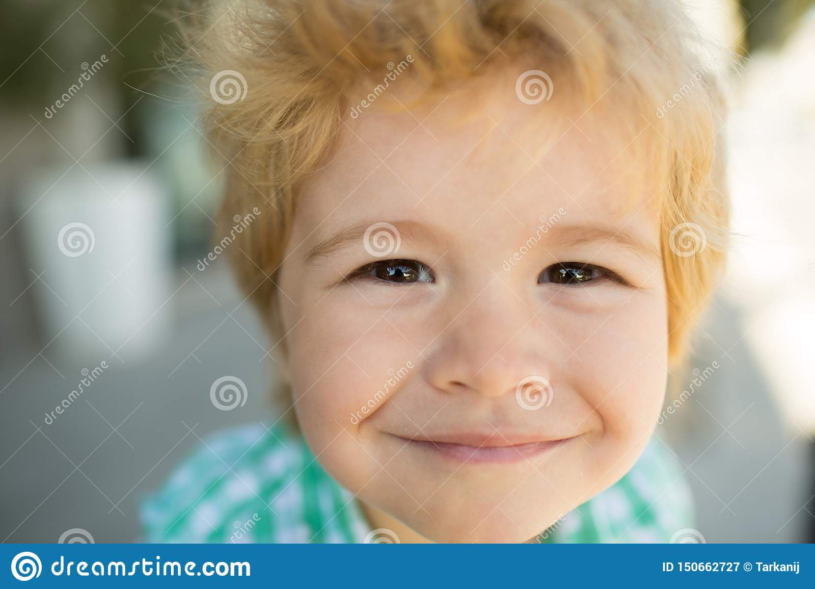 Photo of adorable young happy boy looking at camera. Happy funny child face close up. Super smile from kid. Happiness.