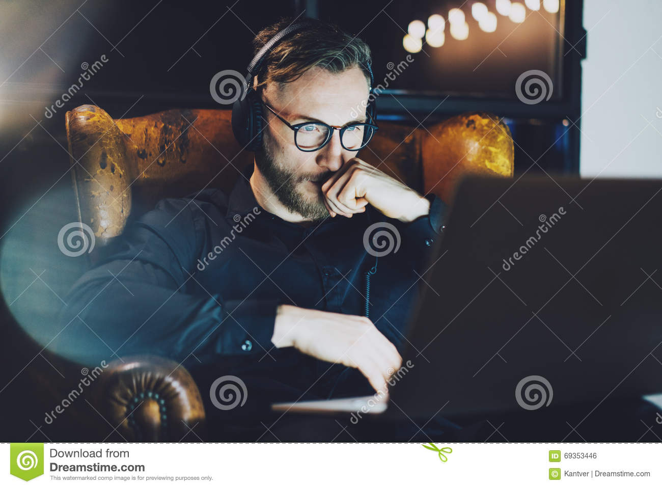 a991e8ceb Photo bearded businessman wearing glasses relaxing modern loft office.Man  sitting in vintage chair,listening music laptop night.Using contemporary  notebook ...