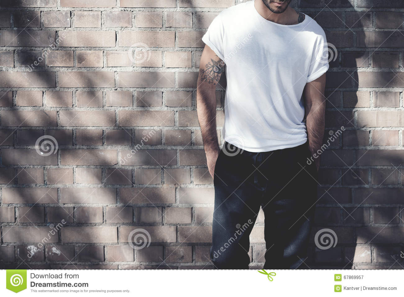 Plain wood table with hipster brick wall background stock photo - Photo Bearded Man With Tattoo Wearing Blank White Tshirt And Black Jeans Bricks Wall Background