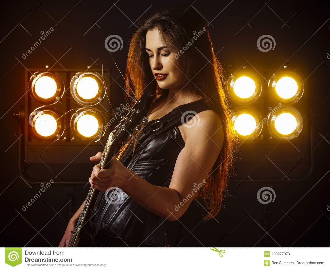 woman playing electric guitar on stage