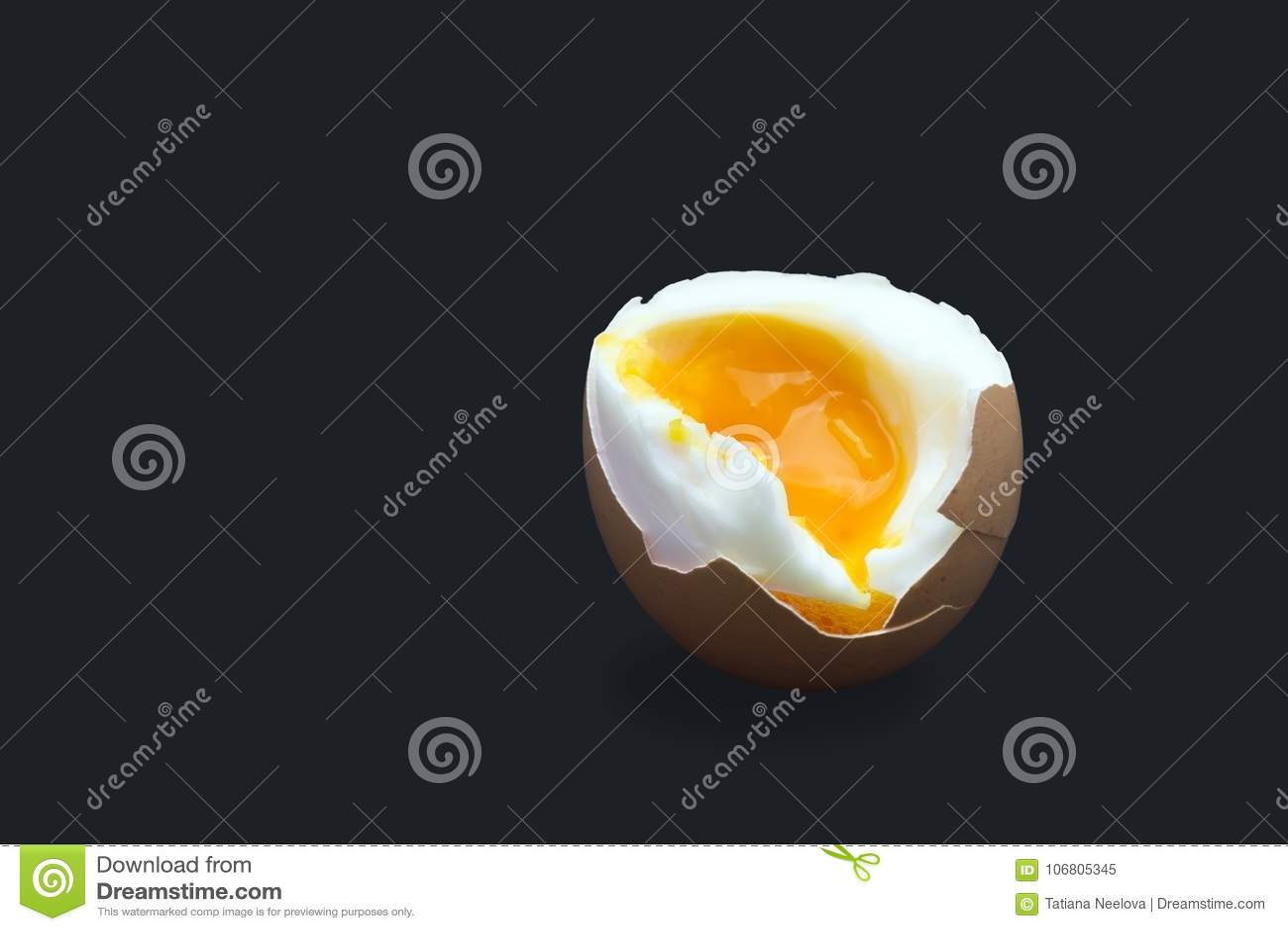 A photo of boiled smash broken hen beige egg isolated on dark blue. Egg`s liquid yolk photo, bright contrast.