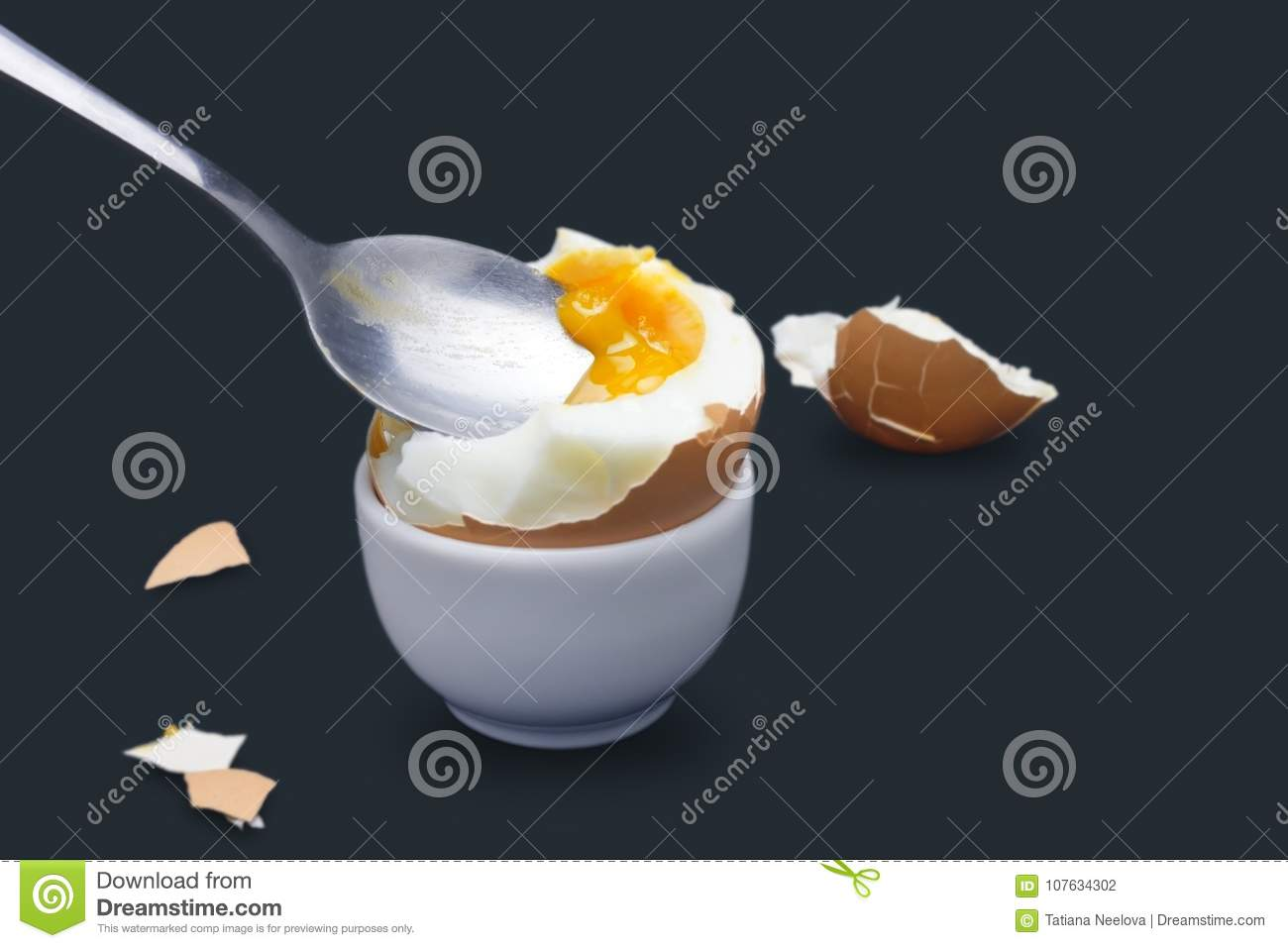 A photo of boiled smash broken hen beige egg and a spoon with yolk on dark blue. Egg`s liquid yolk photo, bright contras