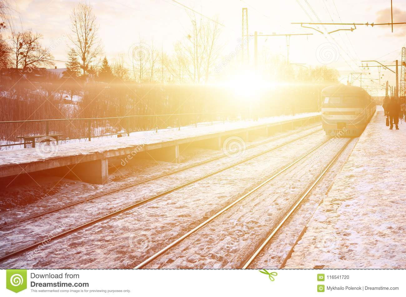 Photo of bright and beautiful sunset on a cloudy sky in cold winter season. Railway track with platforms for waiting trains and p