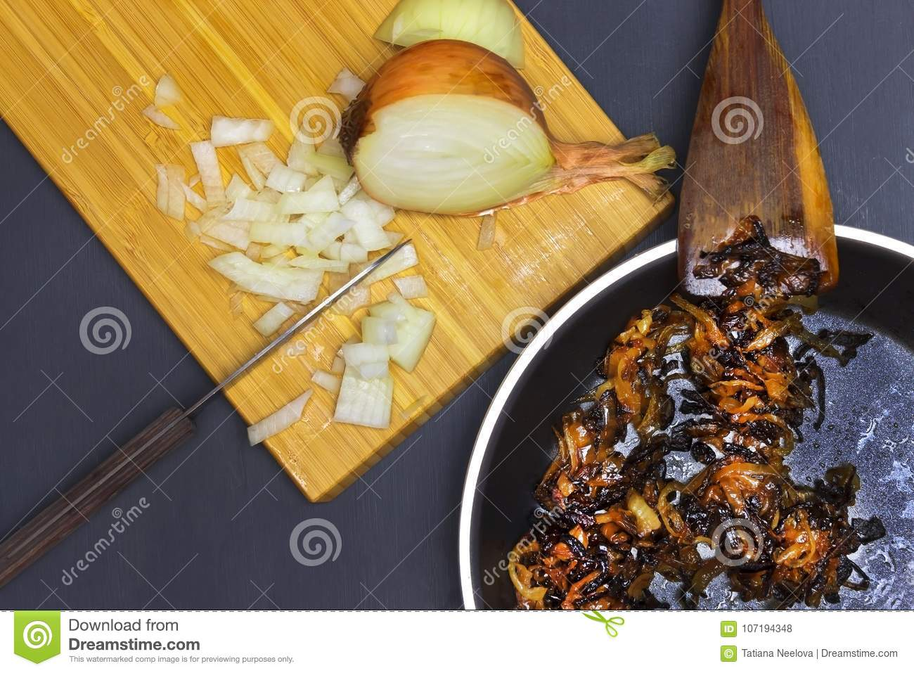 A Photo Of Burnt Onion On The Teflon Pan And Wooden Spatula