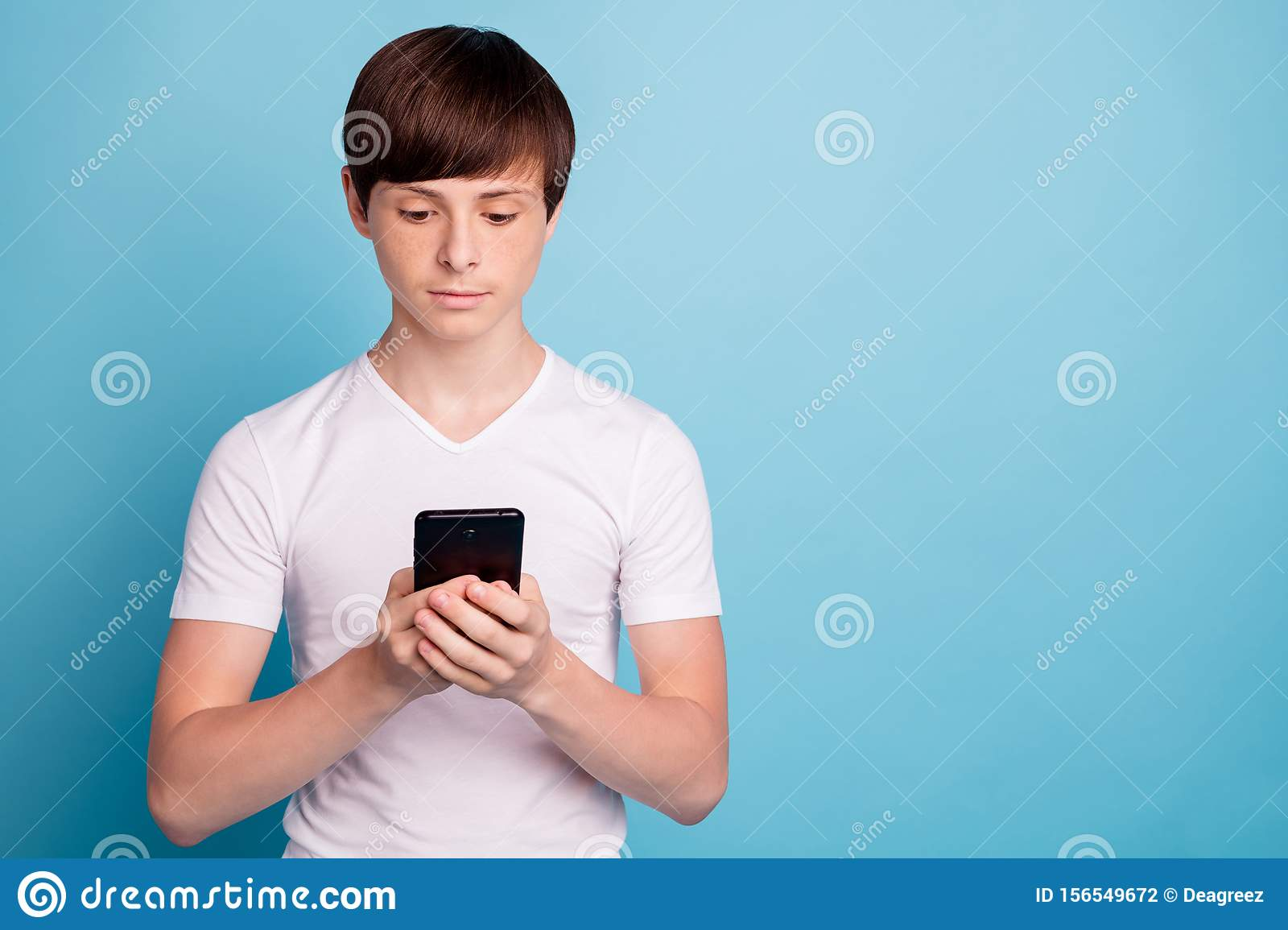 Photo of calm boyfriend browsing through his phone in search of something special while isolated with blue background