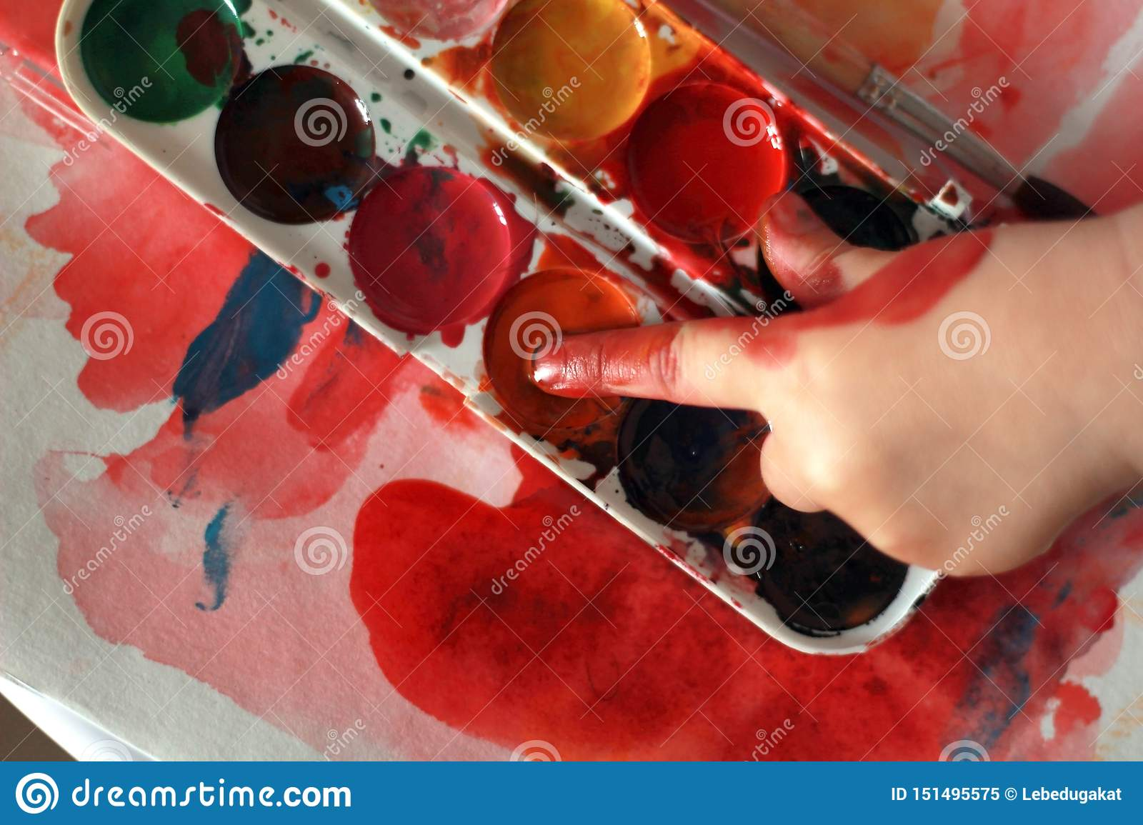 Photo child draws touches the finger with watercolor honey paint