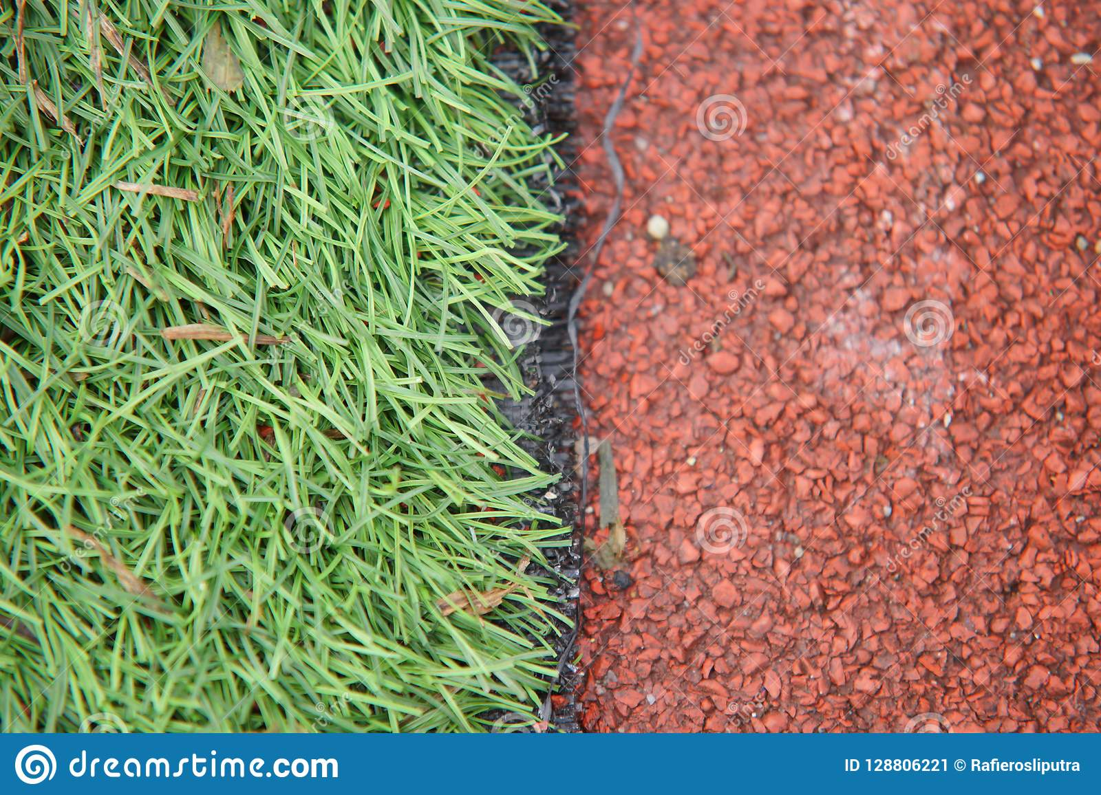 Photo of closeup artificial track and field with green grass combined with artificial grass