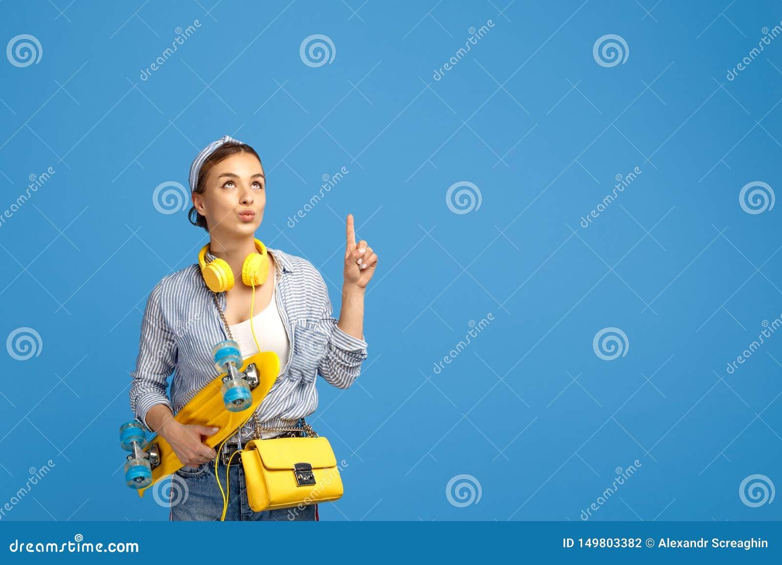 Photo de jeune femme gaie avec les écouteurs jaunes posant avec le penny ou la planche à roulettes et le doigt de point au-dessus