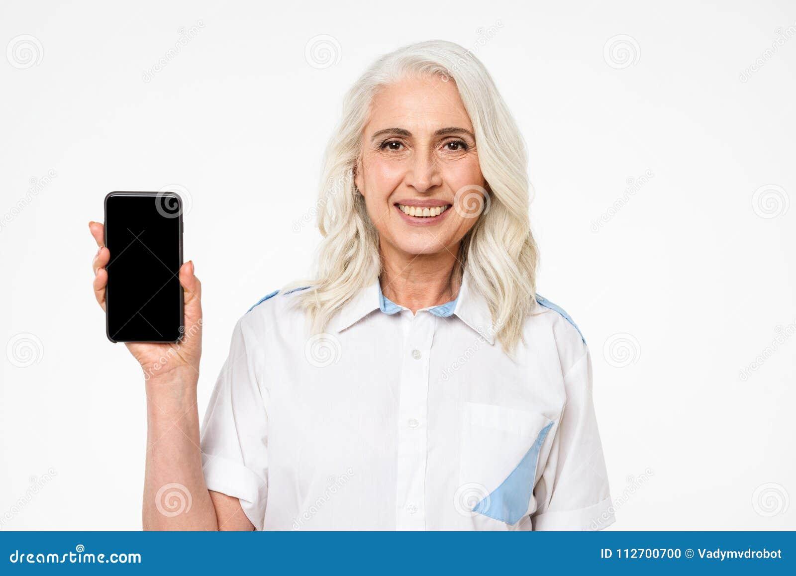 Photo de la femme adulte avec les cheveux gris souriant et faisant le commerci