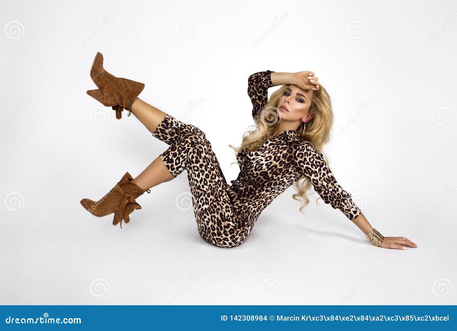 Photo de mode d une belle jeune femme élégante dans une jolie salopette avec la copie animale de léopard et des bottes posant au-
