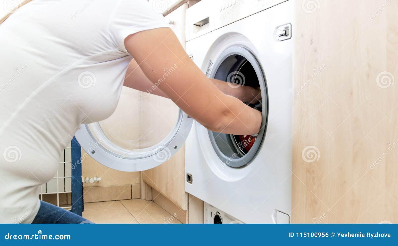 Photo de plan rapproché des mains femelles prenant des vêtements hors de la machine à laver