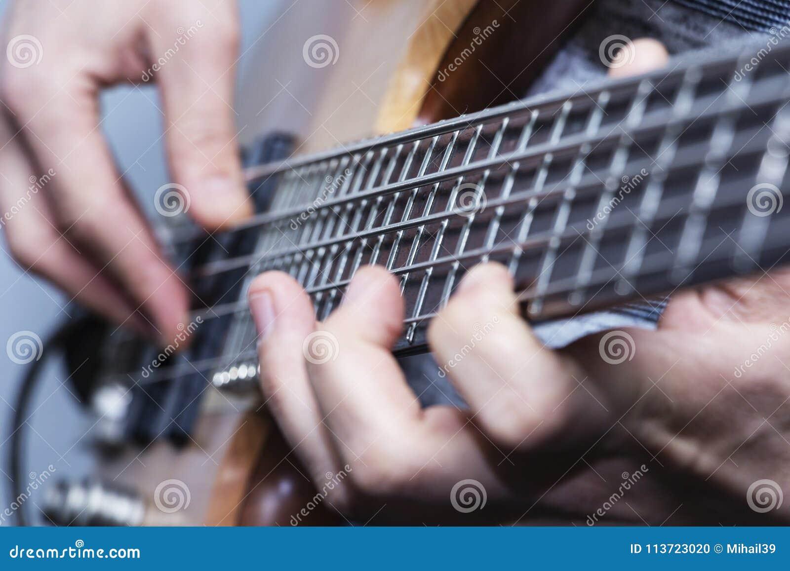 Photo de plan rapproché des mains de joueur de guitare basse, foyer sélectif mou, thème de musique en direct