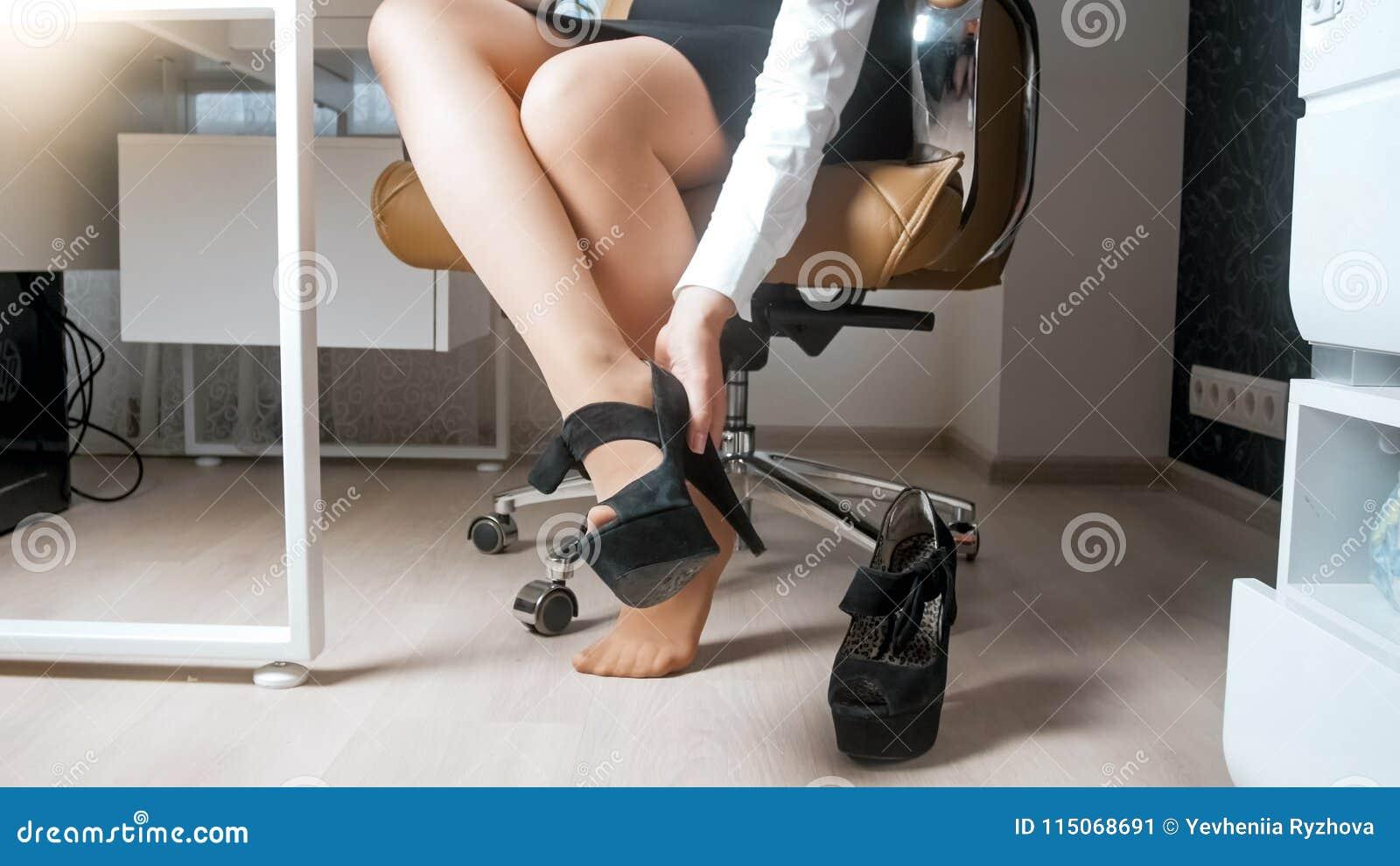 Photo de plan rapproché de la jeune femme d affaires sexy enlevant des chaussures de talons hauts sous la table