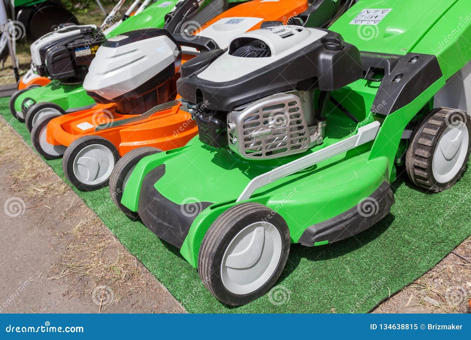 Photo de trois nouveau vert puissant et tondeuse à gazon orange d essence
