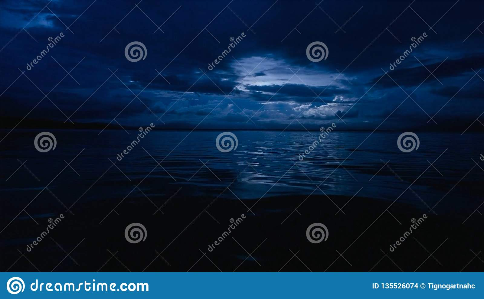 This photo of a deep blue moonlit ocean at night with calm waves