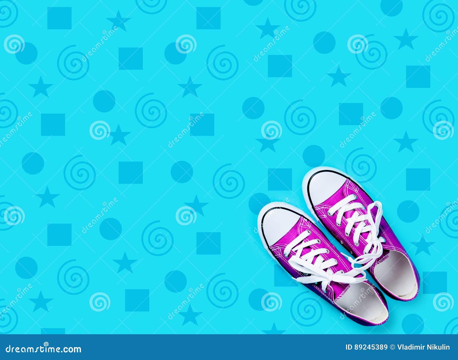 Photo des chaussures en caoutchouc pourpres sur le fond bleu merveilleux