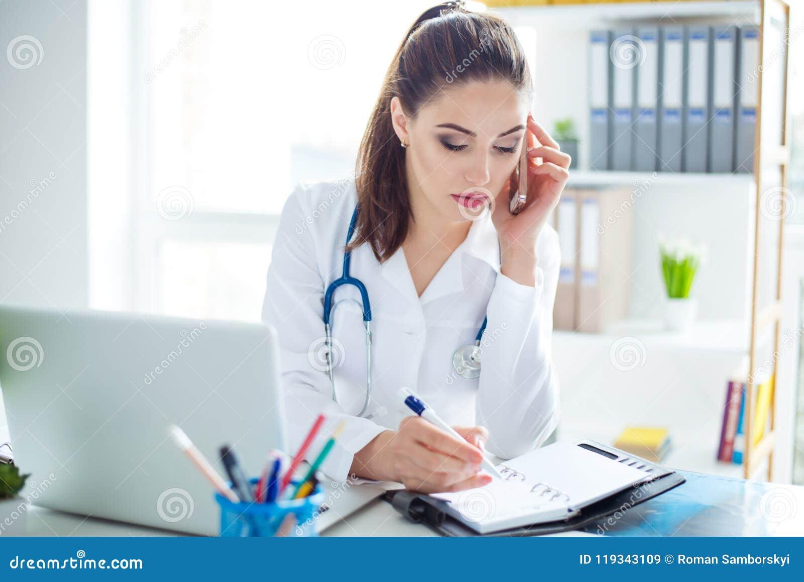 Photo du jeune docteur féminin sûr futé s asseyant au tabl