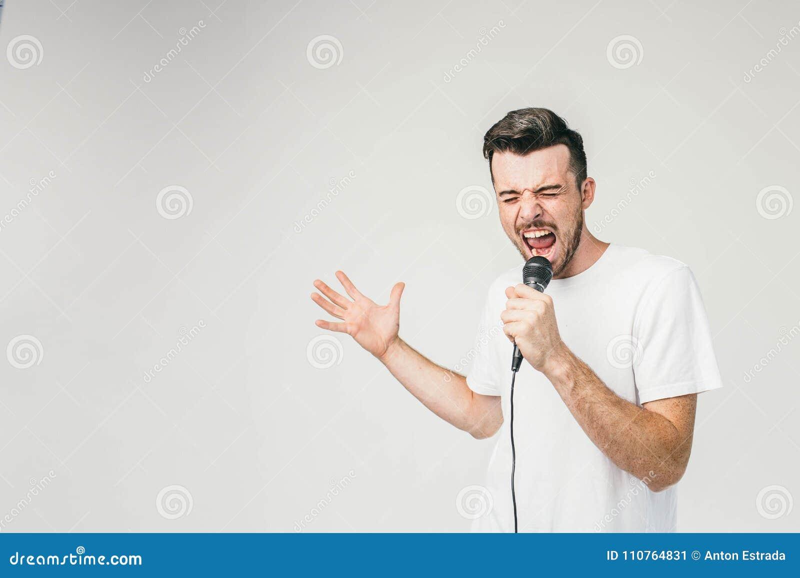 Photo gentille d un type émotif chantant dans le microphone Le sien essayant de faire son meilleur et portées la note la plus éle