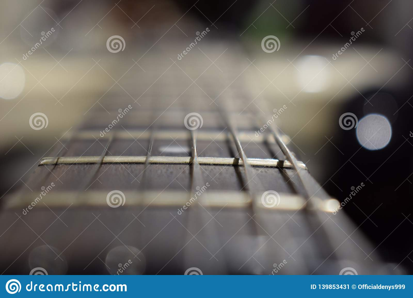 A photo of a guitar neck with strings and a wood texture - the material of a guitar neck. Selective focus on one guitar threshold