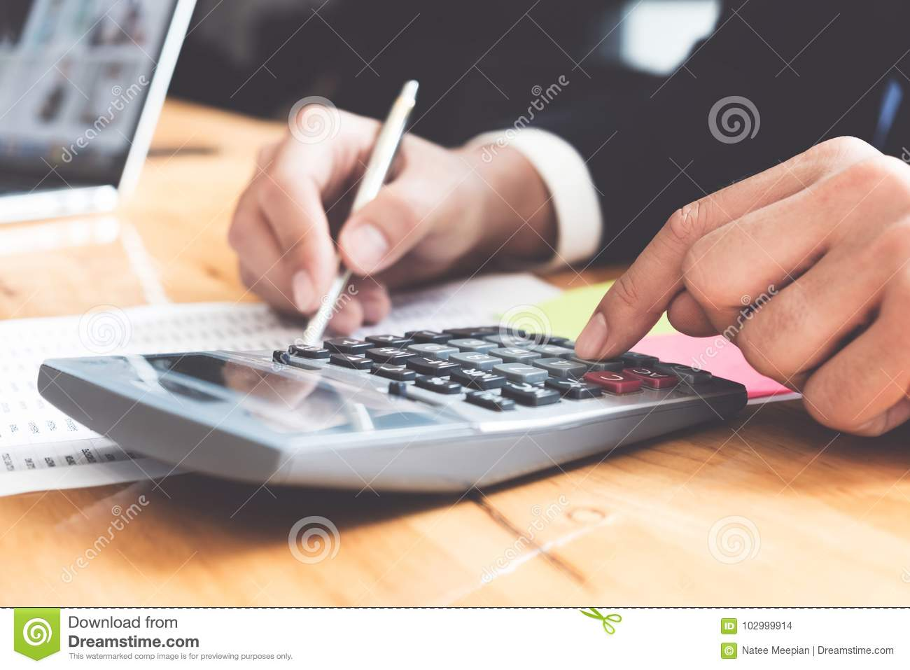 Photo of hands holding pen and pressing calculator buttons over