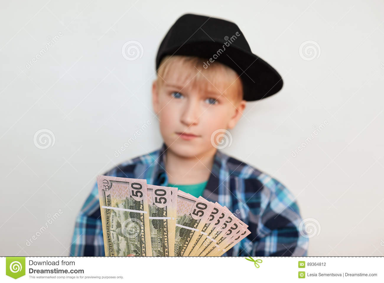 A photo of handsome stylish liitle rich child dressed in black cap and modern shirt holding dollars in his hands. Young businessma
