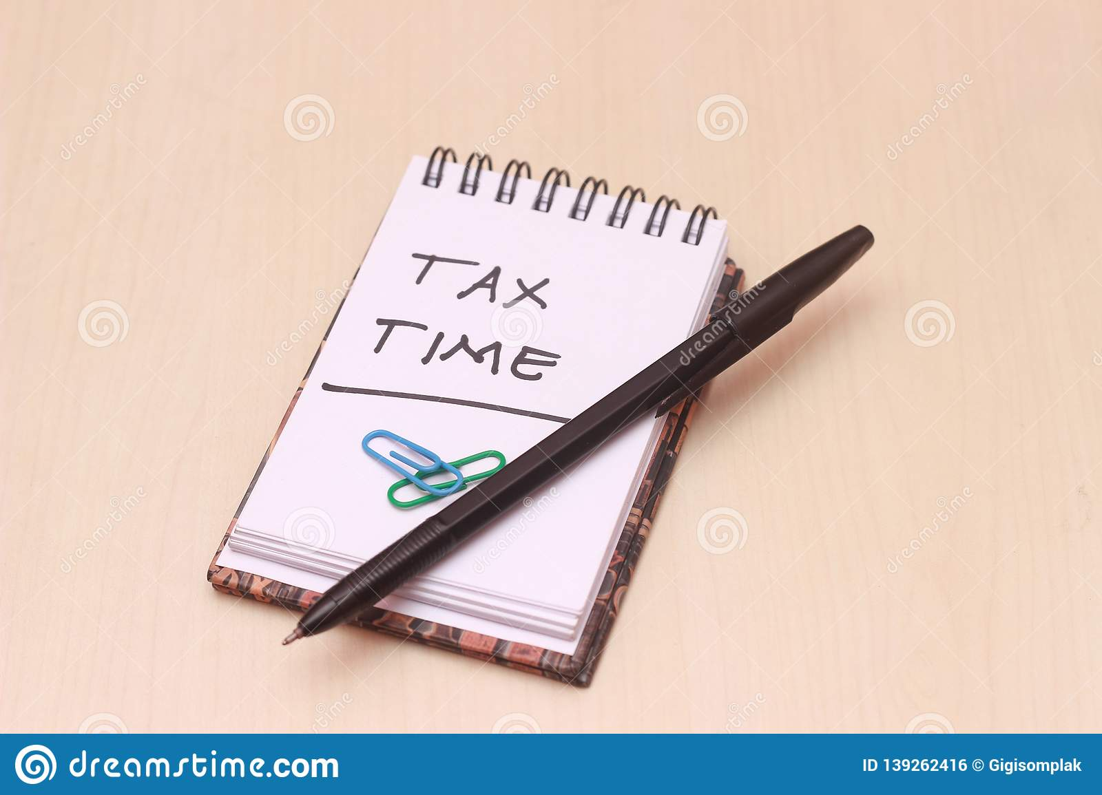 Photo Illustration for Tax Time, block note at wooden table