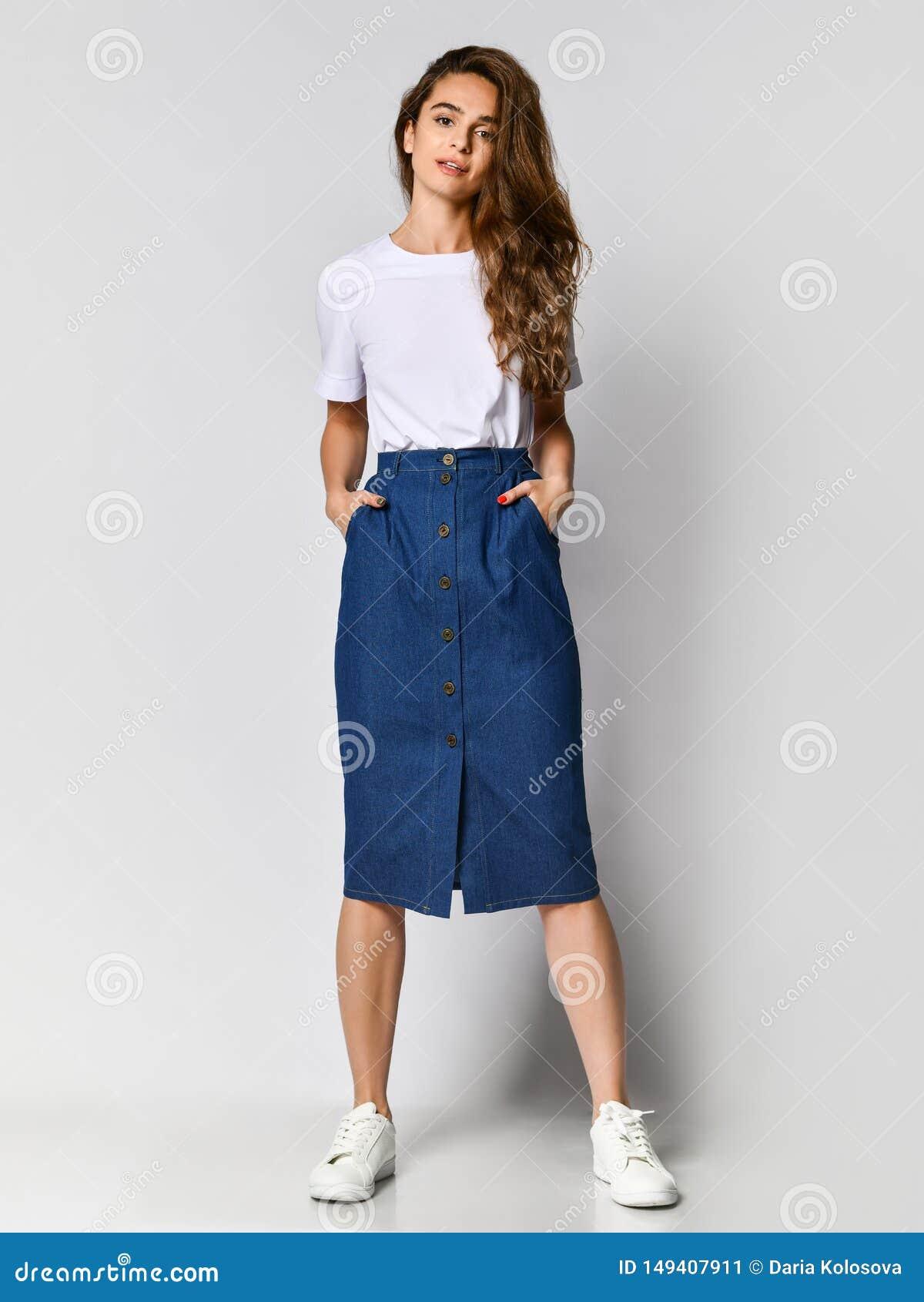 Photo int?grale d une jeune fille de brune avec de longs cheveux dans un chemisier blanc et une jupe bleue Sur un fond clair