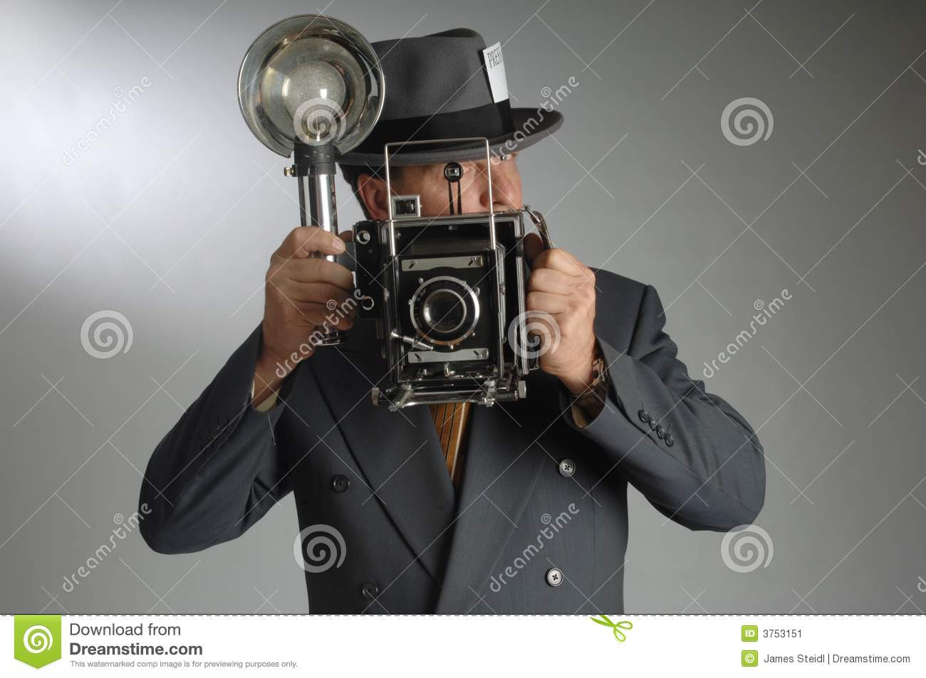 d3160c6824b17 Retro photo journalist wearing a Fedora hat and holding a vintage camera  with flash bulb
